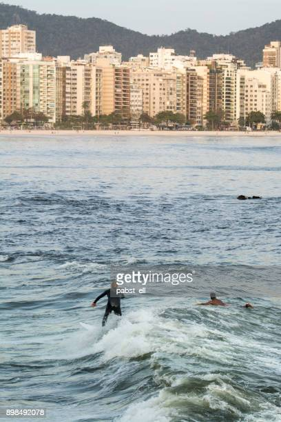 two men surf at icaraí beach in niteroi - niteroi stock pictures, royalty-free photos & images