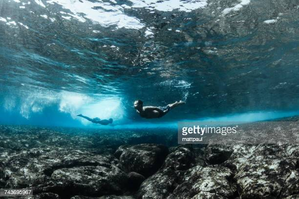 two men swimming underwater in ocean, kalapana, west puna, hawaii, america, usa - kalapana stock pictures, royalty-free photos & images