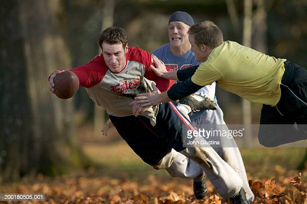 Two men tackling man with football, autumn