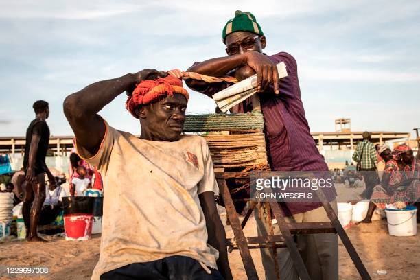Two men take a break at the fishing port in Mbour on November 16, 2020. - Mbour has in the recent months been a popular departure site for illegal...