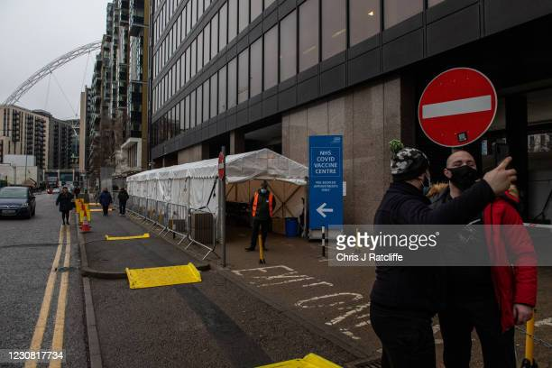 Two men take a selfie outside a Covid-19 vaccination centre near Wembley Stadium on January 27, 2021 in London, United Kingdom. AstraZenecas chief...