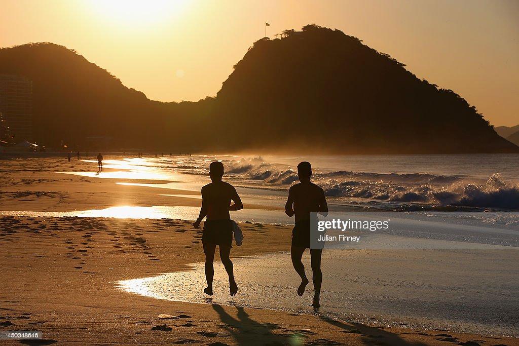 Two men take an early morning jog along Copacabana beach on June 9, 2014 in Rio de Janeiro, Brazil.
