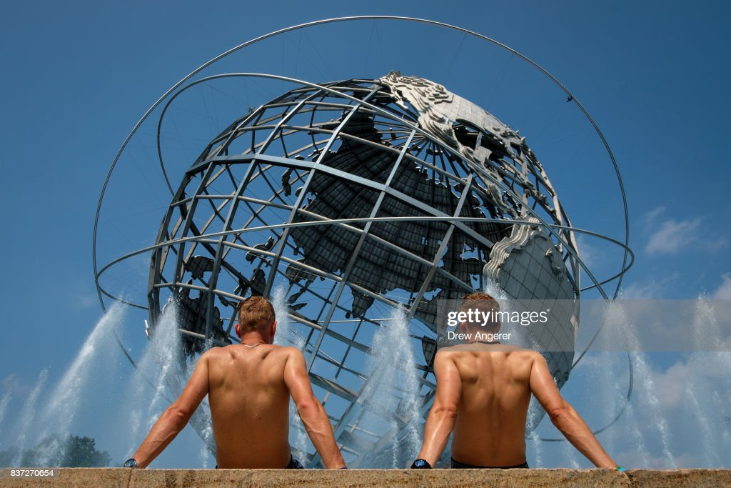 Two men take in the sun at the fountains by the Unisphere steel structure at Flushing Meadows-Corona Park, August 22, 2017 in the Queens borough of New York City. With heat index values near 100, the New York City area is under a heat advisory on Tuesday.