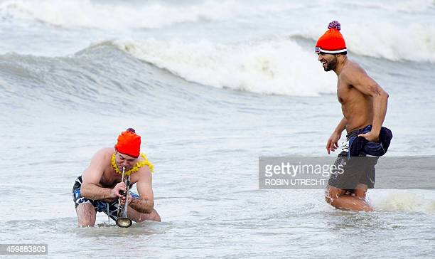Two men take part in the traditional sea bathing to mark the start of the new year on January 1 2014 in Scheveningen AFP PHOTO/ANP/ ROBIN UTRECHT...
