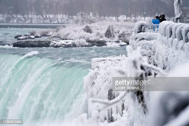 Two men take photographs at the Horseshoe Falls in Niagara Falls, Ontario, on January 27, 2021.