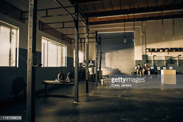 two men taking a break from training in gymnasium - focus on background stock pictures, royalty-free photos & images