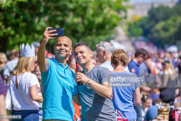 two men taking a selfie in windsor great park while celebrating the marriage of meghan markle and prince harry at st george's chapel at windsor castle. - meghan stock photos and pictures