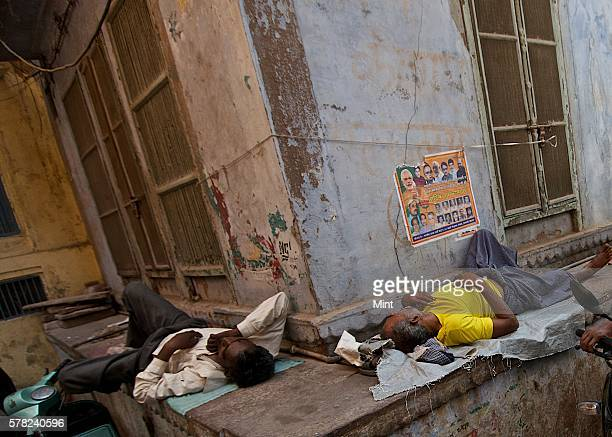 Two men taking a short nap on April 26 2016 in Varanasi India Summers in India are not for the fainthearted During the afternoons the temperature in...