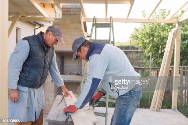 Two men taking meaurements of wooden plank outdoor