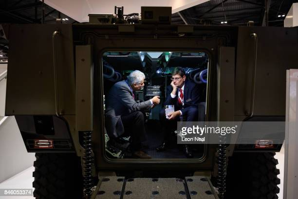 Two men talk as they sit inside a VBCI amoured personel carrier at the DSEI event at the ExCel centre on September 12 2017 in London England The...