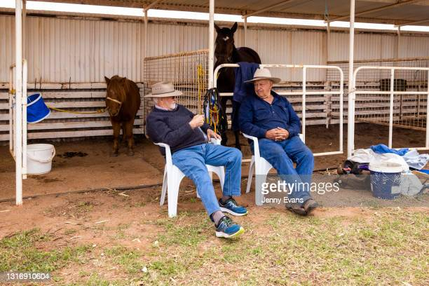 Two men talk in the horse stalls during the Cobar Races at Cobar Miners' Race Club on May 08, 2021 in Cobar, Australia. The race meet is held...