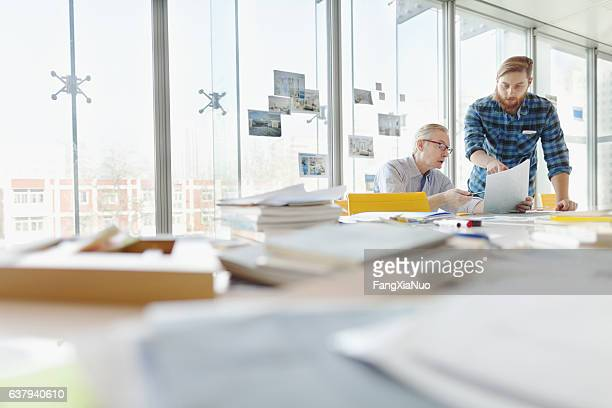 two men talking about ideas in office planning studio - copyright stock photos and pictures