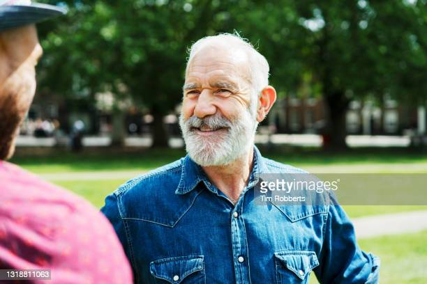 two men talking and smiling, outside - white hair stock pictures, royalty-free photos & images