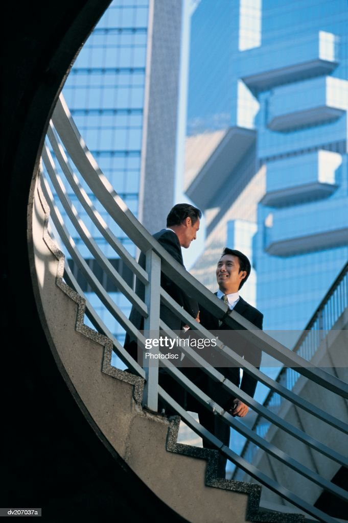 Two men talking and standing on stairs : Stock Photo