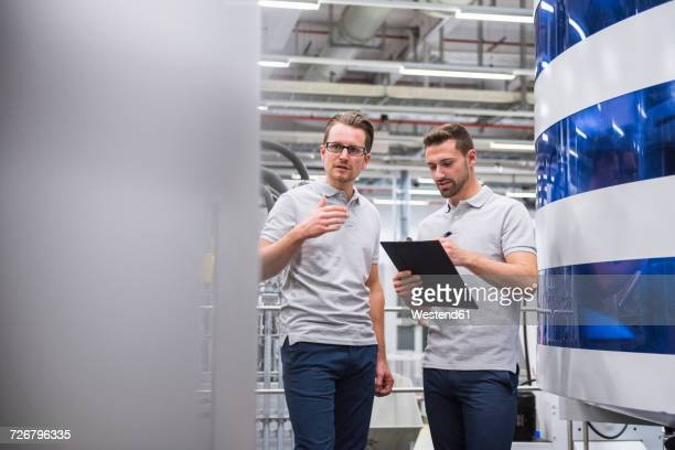 Two men talking at machine in factory shop floor