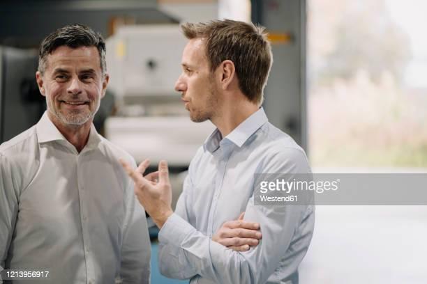 two men talking in a factory - maschinenteil hergestellter gegenstand stock-fotos und bilder