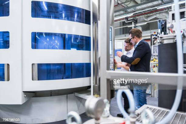Two men talking in factory shop floor looking at screen