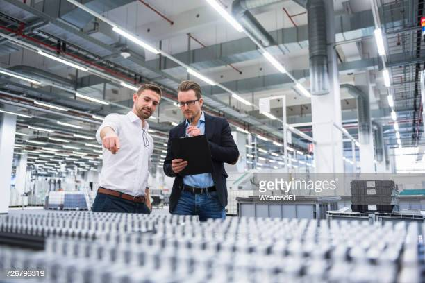 two men talking in factory shop floor - hergestellter gegenstand stock-fotos und bilder