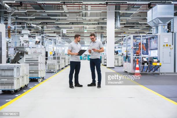 two men talking in factory shop floor - polo shirt stock pictures, royalty-free photos & images