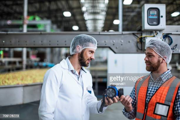 Two men talking in food processing plant