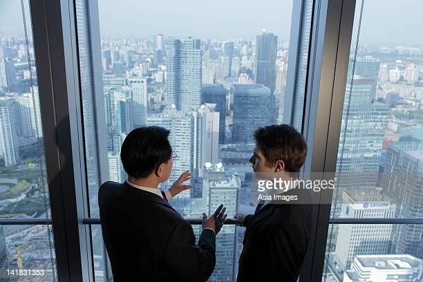Two men talking in front of window with a view of the city of Beijing