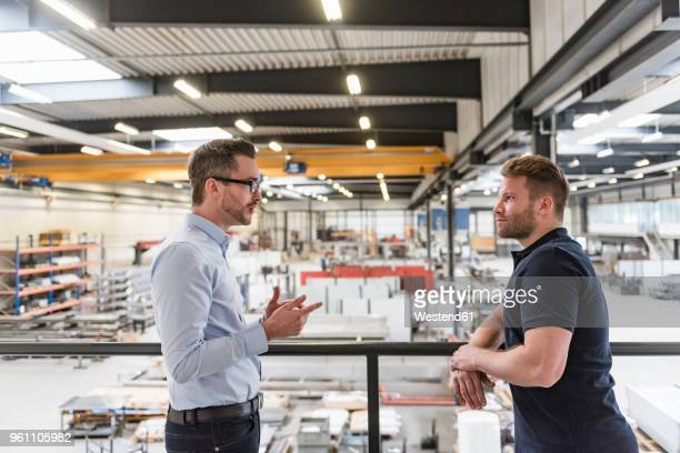 two men talking on factory shop floor - 見渡す ストックフォトと画像