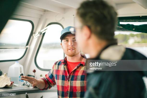 two men talking on fishing boat on coast of maine, usa - heshphoto imagens e fotografias de stock