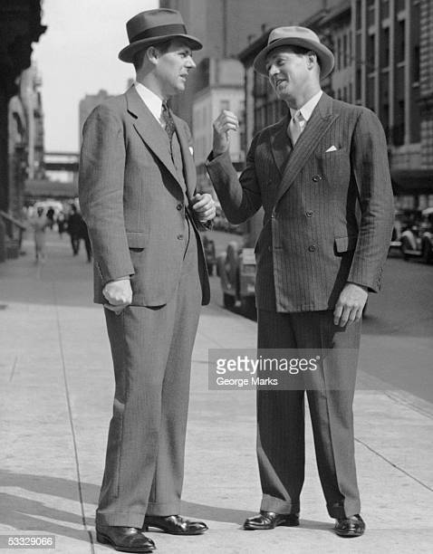Two men talking on street