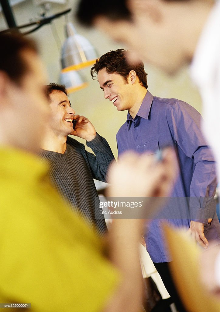 Two men talking, one using cell phone : Stockfoto