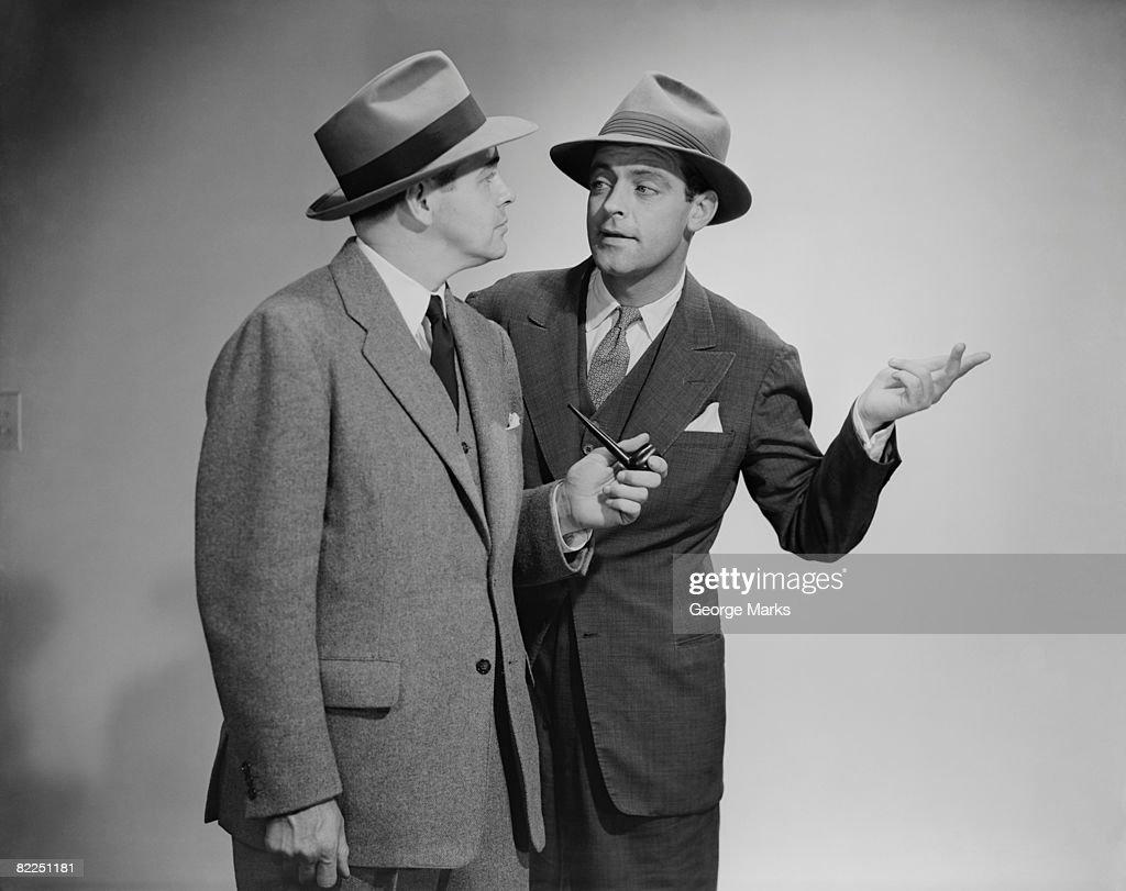 Two men talking, studio shot : Stock Photo