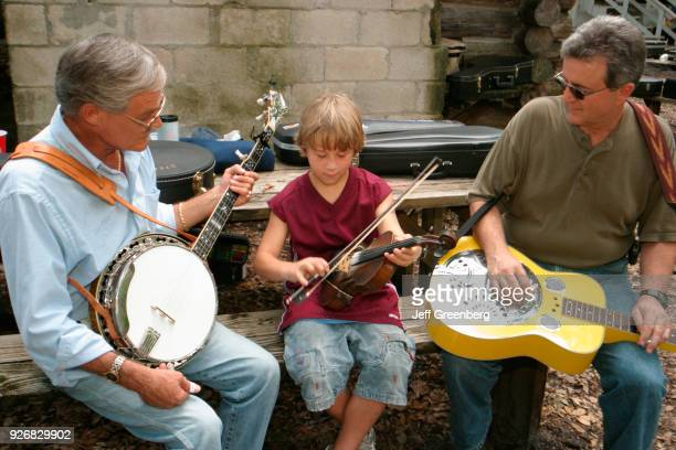 Two men teach a boy how to play a fiddle at the South Florida Bluegrass Association monthly festival