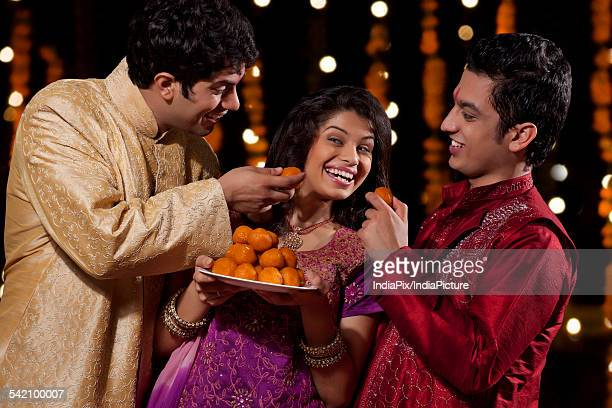 two men tempting woman to eat sweets - mithai stock pictures, royalty-free photos & images