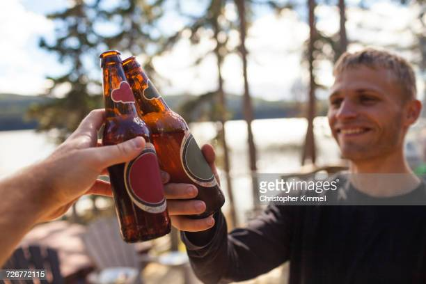 Two Men Toast With Their Beer Bottles During A Weekend Trip To The Lake