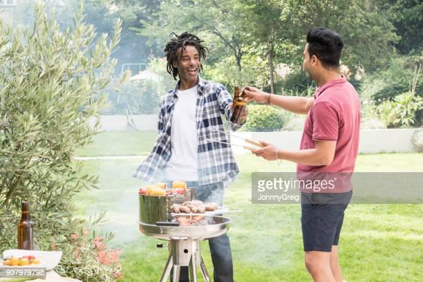 Two men toasting beer bottles in garden with bbq