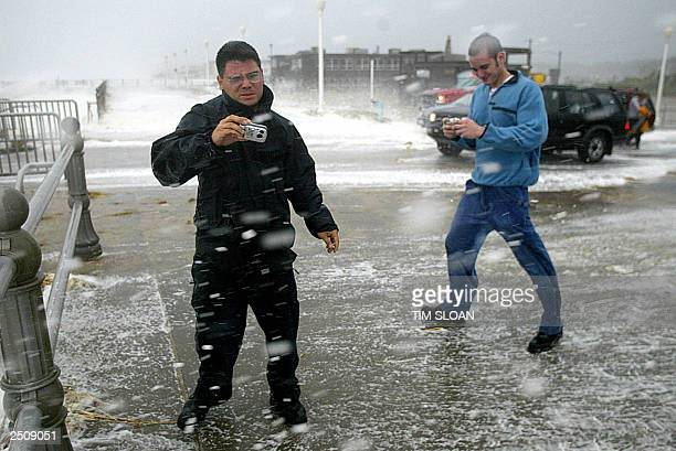 Two men try to take photographs of the wild surf along the boardwalk during Hurricane Isabel 18 September Virgina Beach Virgina Isabel lashed the US...