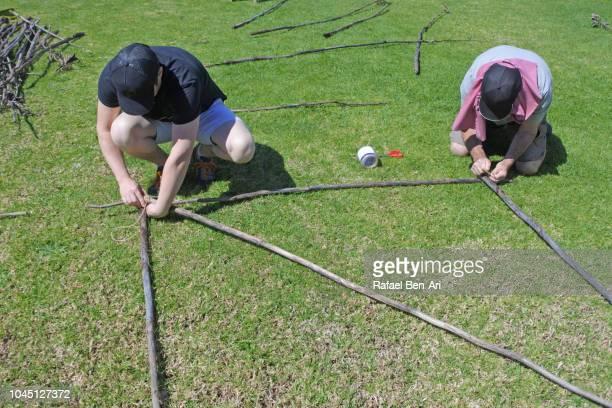 two men tying knots on pieces of wooden poles - rafael ben ari ストックフォトと画像