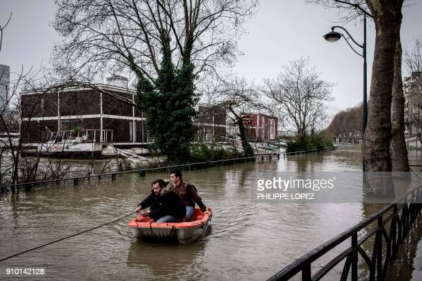 Two men use a dinghy as they leave a housebout on the flooded banks of the river Seine in Paris on January 25 2018 The Seine continued to rise on...