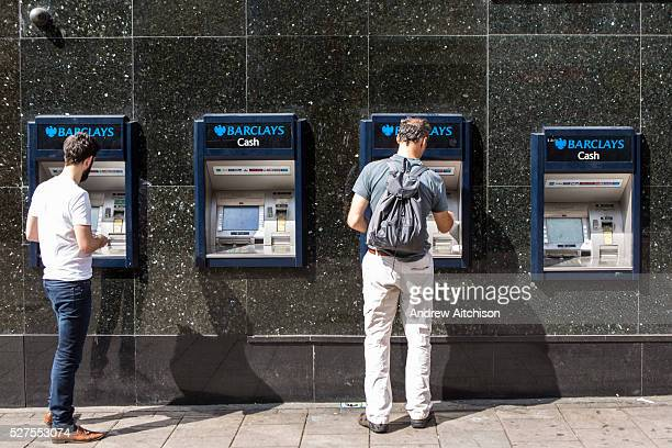 Two men using a Barclays cash machine on a street in London United Kingdom These machines are called automated teller machine or automated banking...