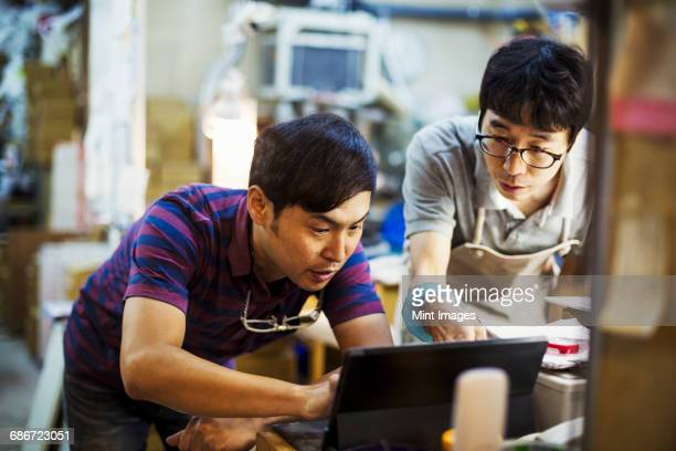 Two men using a laptop computer, working together in a glass makers workshop.