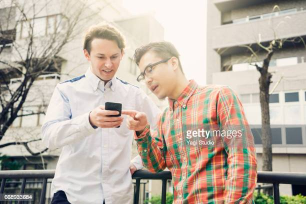 Two men using a smart phone in city