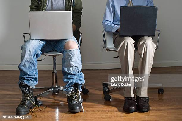 Two men using laptop, low section