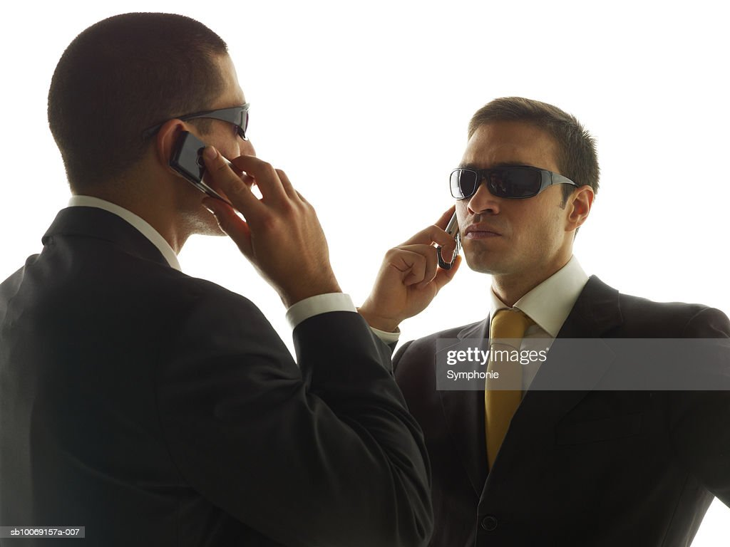Two men using mobile phone against white background : Stockfoto