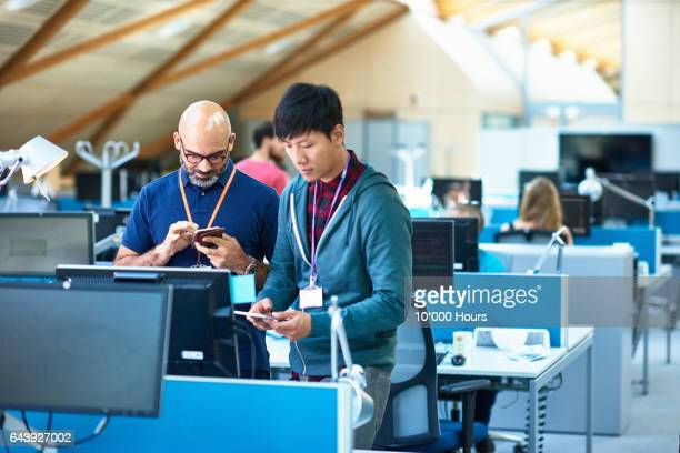 Two men using mobile phones in modern office.