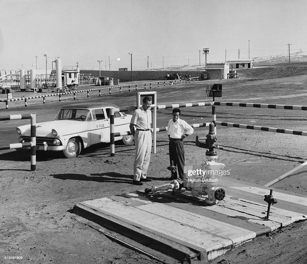Two men view the site of the Arabian American Oil Company's first successful oil well in Saudi Arabia. | Location: Dharan, Saudi Arabia.