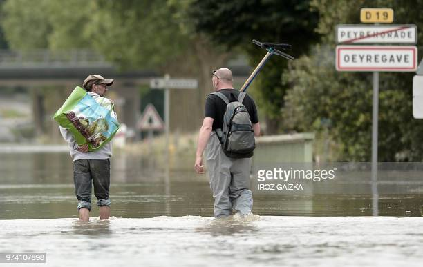 Two men wade through flood waters on June 14 2018 following heavy rains in Peyrehorade in the region of Landes France