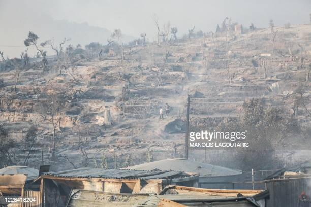 Two men walk amid smoke inside the burnt camp of Moria on the island of Lesbos after a major fire broke out, on September 9, 2020. - Thousands of...