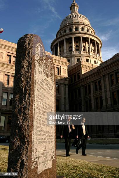 Two men walk between a monument to the Ten Commandments and the Texas State Capital in Austin Texas Thursday February 17 2005 The monument was...