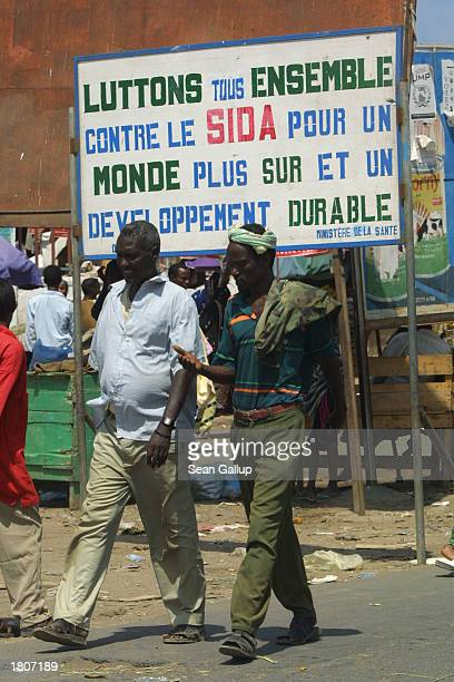 Two men walk by a sign that reads 'We must struggle together against AIDS for a more secure world and sustainable development' February 21 2003 in...