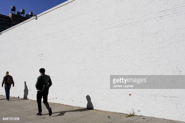Two men walk by an empty white wall in Manhattan