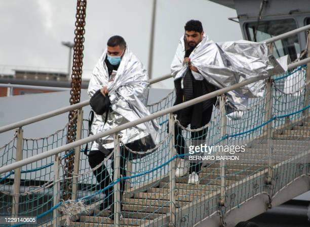 Two men walk down a ramp as they leave a rescue boat on October 18, 2020 in Calais, after they were rescued with 15 others off the northern French...